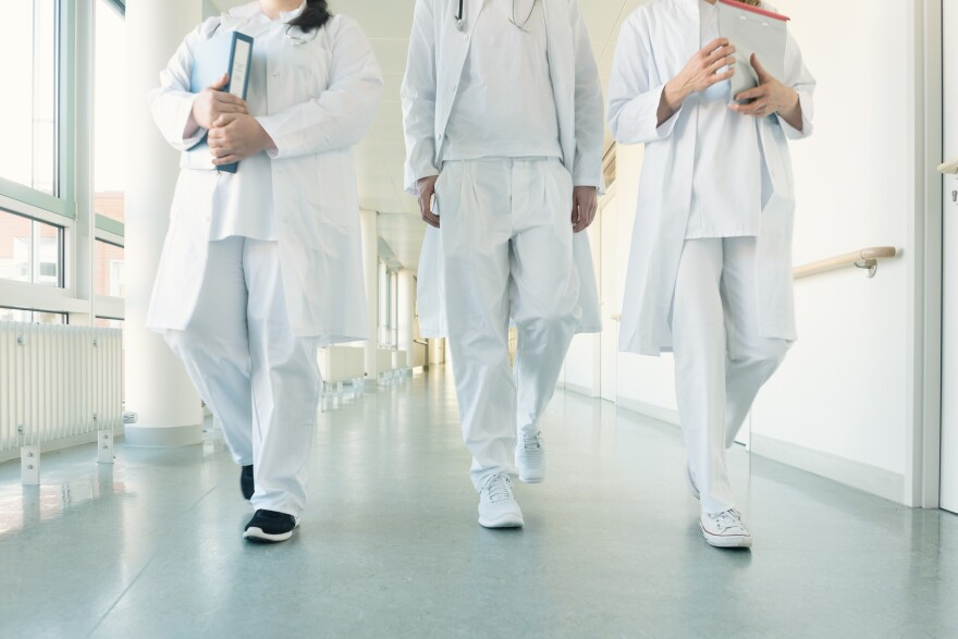 Stock image of three doctors walking in a hospital hallway
