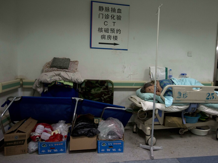 A patient rests on a bed in the corridor of a crowded hospital in Beijing.
