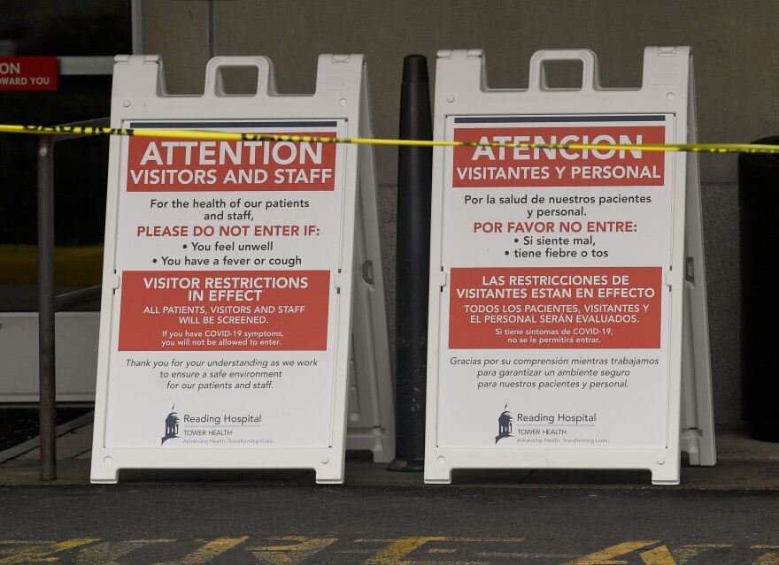 Signs in English and Spanish outside a hospital in West Reading, Pa., advertise visitor restrictions as a precaution against the spread of COVID-19.