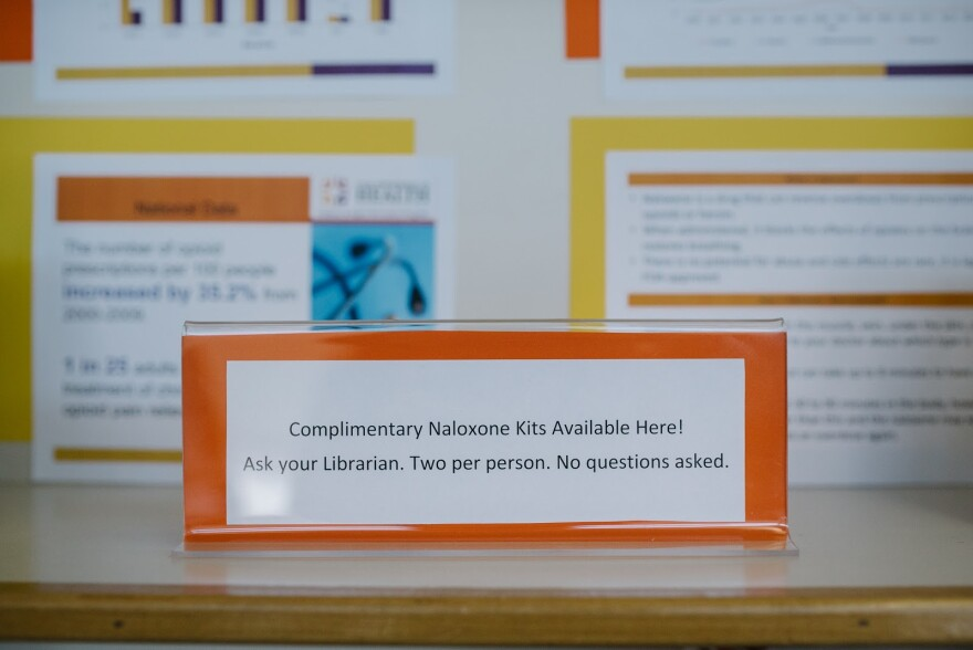 """Sign reads """"Complimentary naloxone kits available here. Ask your librarian. Two per person. No questions asked."""""""