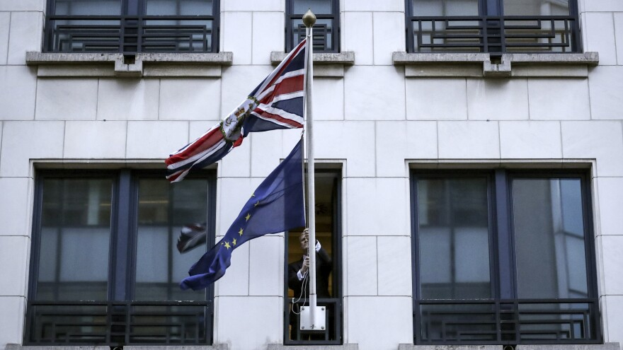 An official removes European Union flag from the British diplomatic post in Brussels on Friday.