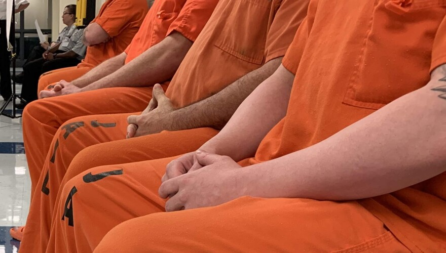 A row of men in orange jail jumpsuits sit with their hands clasped