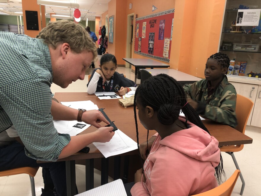 UF doctoral student Sean Moran shows a seventh grader at Roosevelt Middle School in West Palm Beach how to measure and calculate the size of a megalodon tooth.