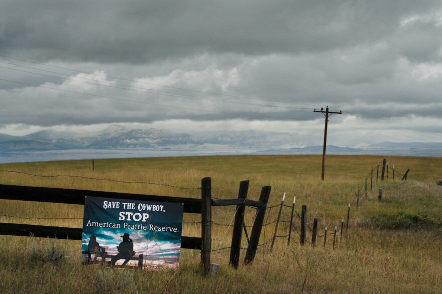 "A ""Save the Cowboy"" sign is posted along a fence. The ""Little Rockies"" on the Fort Belknap Indian Reservation are seen in the distance."