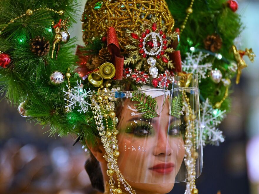 A model dressed as a Christmas tree and wearing a face shield poses for photos in a shopping mall in Bangkok on Dec. 24, 2020.