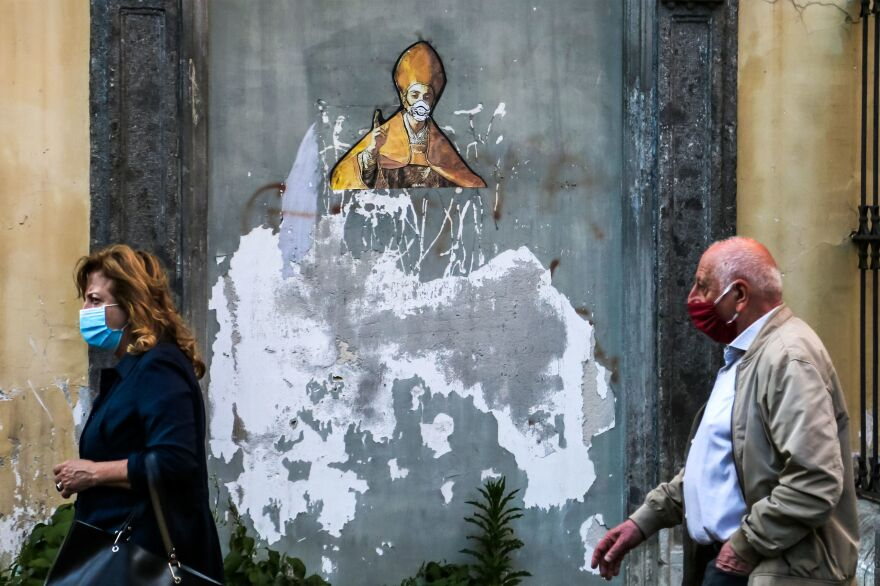 Pedestrians in face masks pass a mural in Naples depicting the city's patron saint, St. Gennaro, in a face mask too. Italy has set a timeline for lifting its strict coronavirus travel restrictions, after its outbreak overwhelmed medical centers across the country earlier this year.
