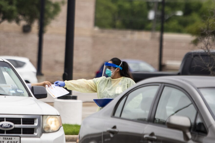 A worker handles paperwork at CommUnityCare's drive-thru coronavirus testing site at the Hancock Center.