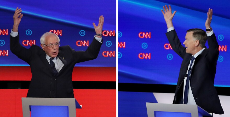 Democratic presidential candidate Sen. Bernie Sanders (left) gestures while former Colorado governor John Hickenlooper (right) speaks during the Democratic Presidential Debate at the Fox Theatre in Detroit, Michigan.