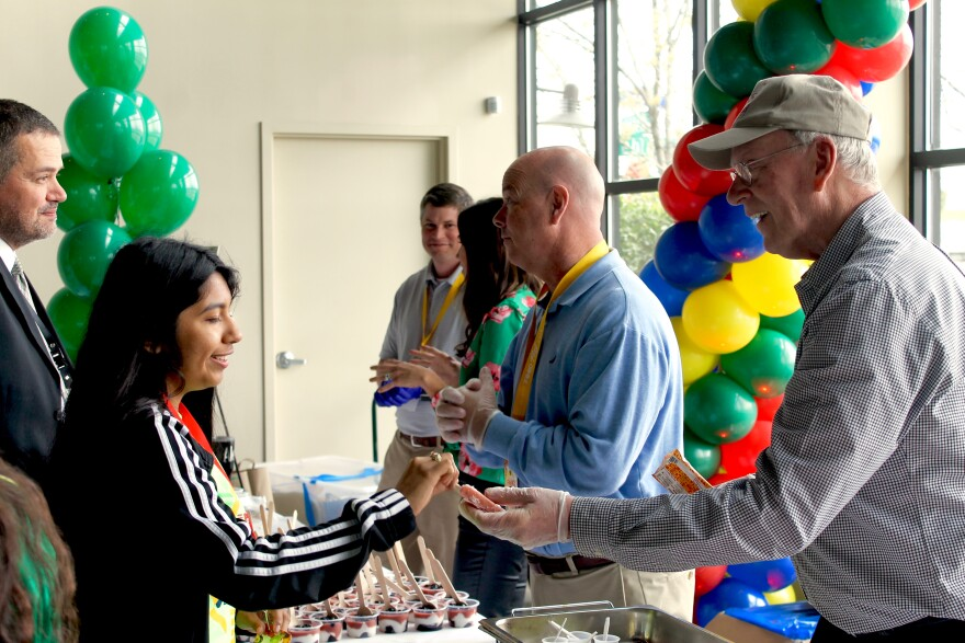 Food distributor Marty Renaud (right) hands a fruit popsicle to eighth grader Mia Martinez at Dallas ISD's Fresh Food Fest on March 28, 2019.