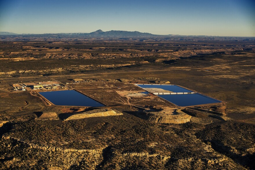 An aerial image shows two large ponds of uranium tailings with Sleeping Ute Mountain in the background.