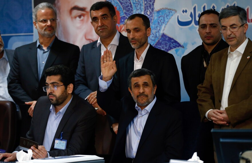 Former President Mahmoud Ahmadinejad raises his hand Wednesday as he registers to run in Iran's presidential election next month.
