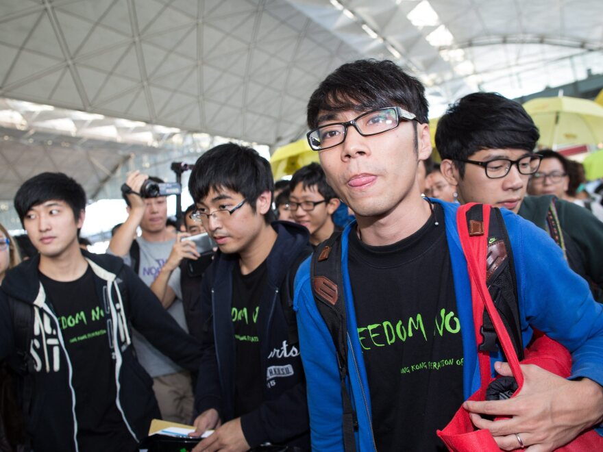 Federation of Students representatives Alex Chow Yong-kang (second left), Eason Chung Yiu-wa (second right) and Nathan Law Kwun-chung (right) talk to the media before trying to board a plane to Beijing on Saturday. They were told that Beijing authorities had revoked their travel documents.