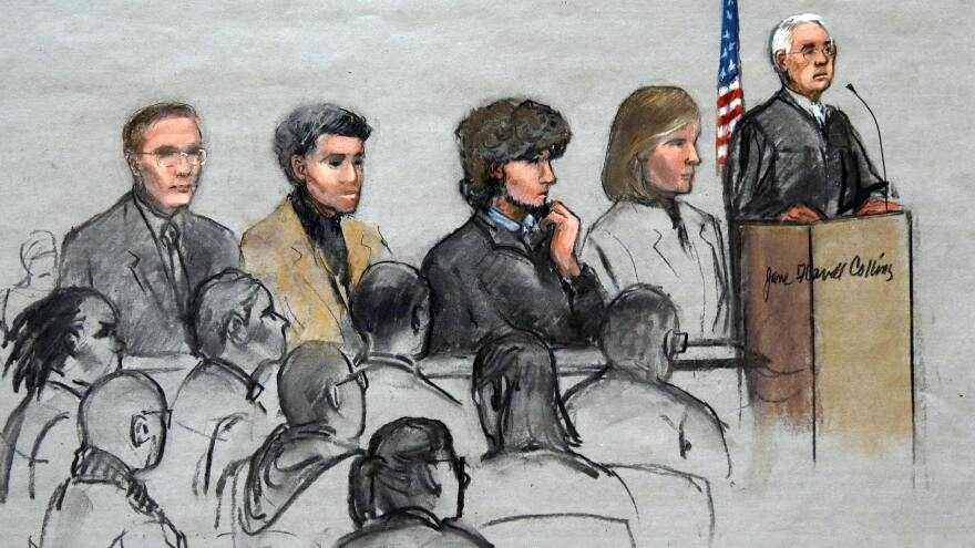 In this courtroom sketch, Boston Marathon bombing suspect Dzhokhar Tsarnaev (third from right) is depicted with his lawyers and U.S. District Judge George O'Toole Jr., as O'Toole addresses a pool of potential jurors. The trial begins Wednesday.