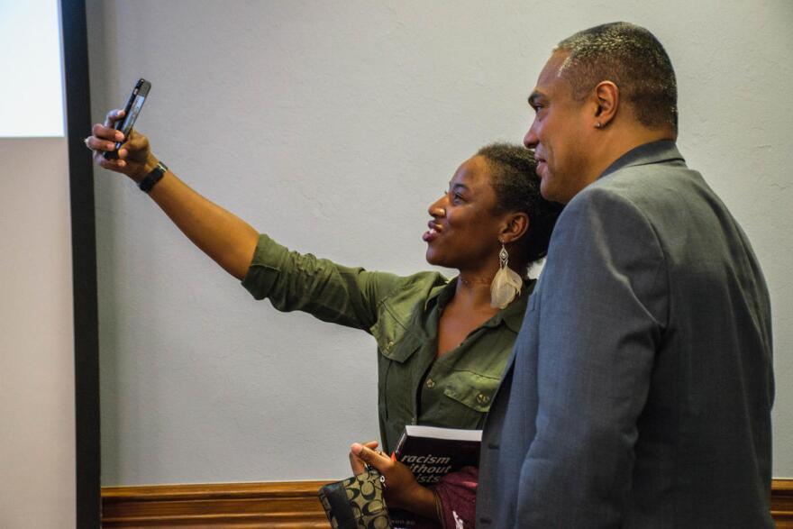"Bonilla-Silva poses for a selfie with one of the talk's student attendees, who just had him sign her copy of ""Racism Without Racists."""