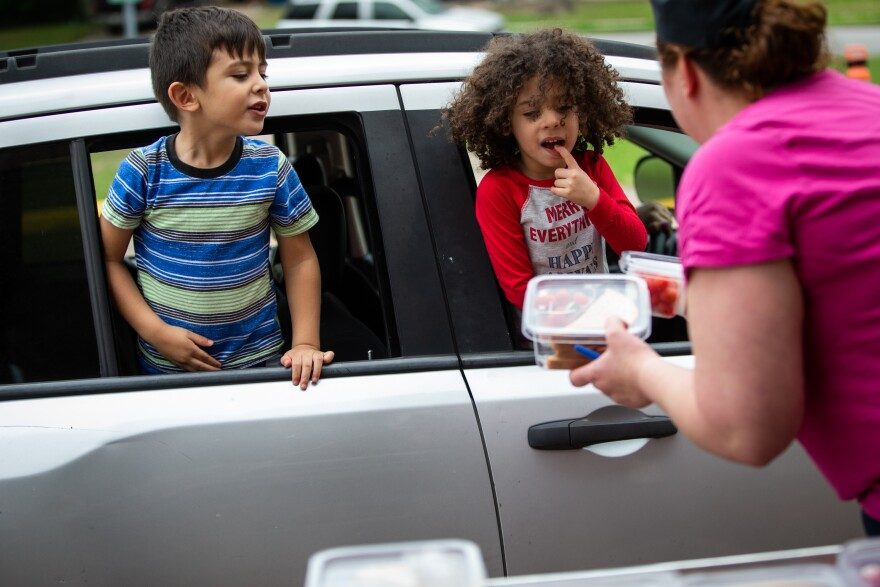 Milan, 4, and Myden, 3, select meals from Austin ISD, which is passing out curbside lunches while schools are closed.