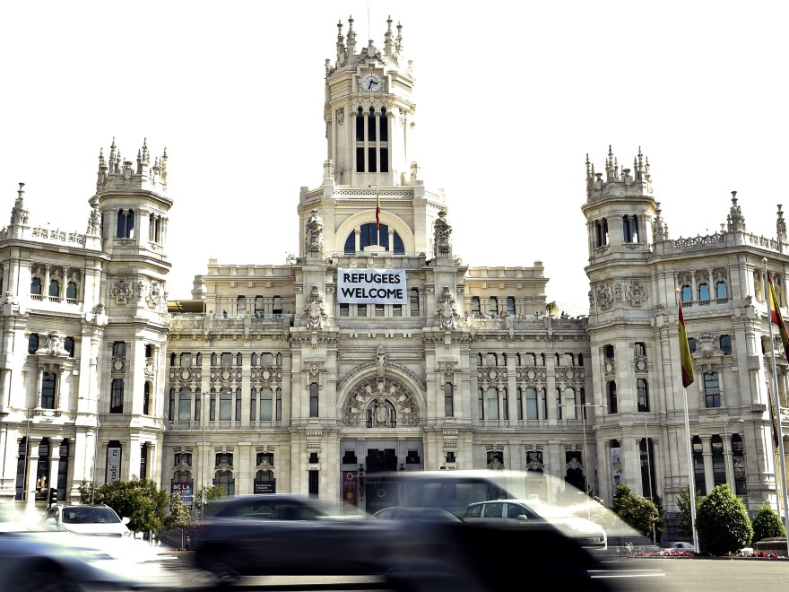 """A banner reading """"Refugees welcome"""" hangs on the facade of the Madrid City Hall."""