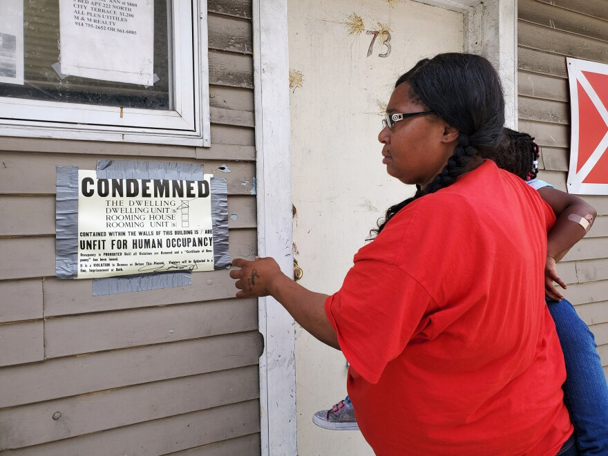Carla Johnson reads one of many condemned notices in the city of Newburgh, N.Y., where tenants say they need universal rent regulations to force landlords to maintain apartments.