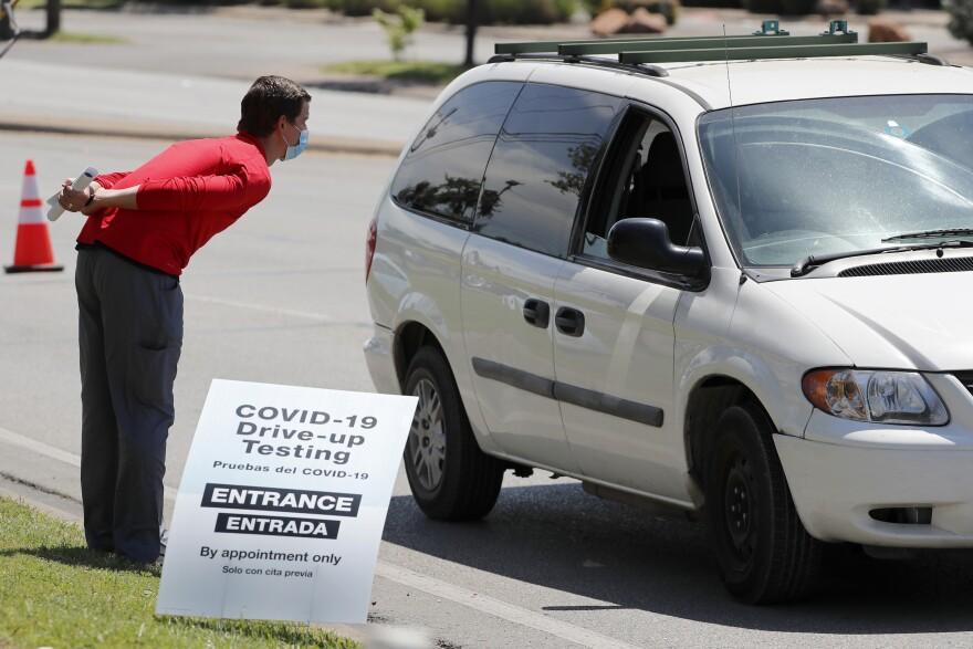 Walgreens employee talks to person in mini van