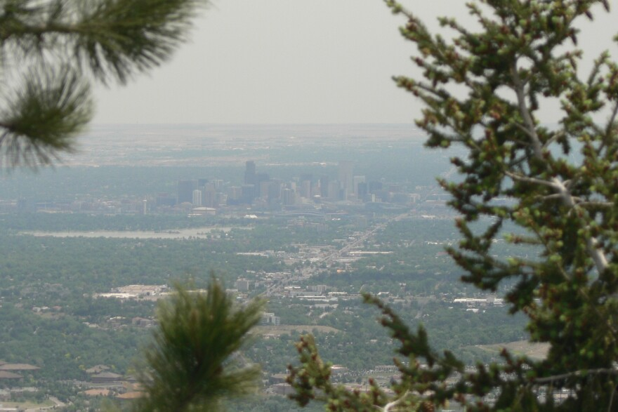 A cloud of smog hangs over Denver in the distance.