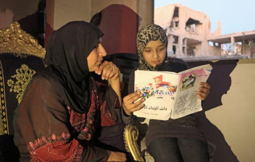 A young girl named Islam reads a book to her mother.