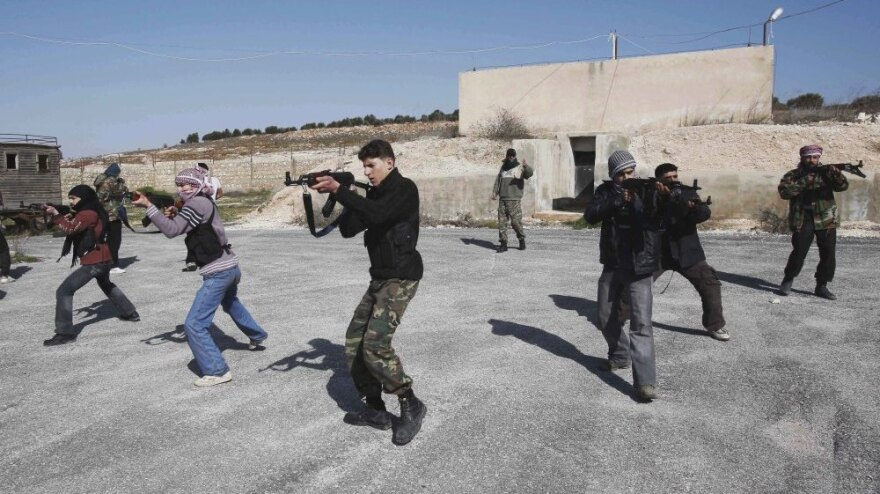 Syrian rebels aim during a weapons training exercise outside Idlib, Syria on Tuesday. Syrian government forces renewed their assault on the rebellious city of Homs on Tuesday in what activists described as the heaviest shelling in days.