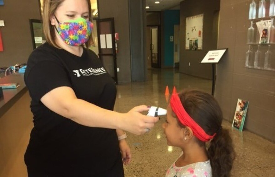A Valley of the Sun YMCA staff member takes the temperature of a child before she enters child care.