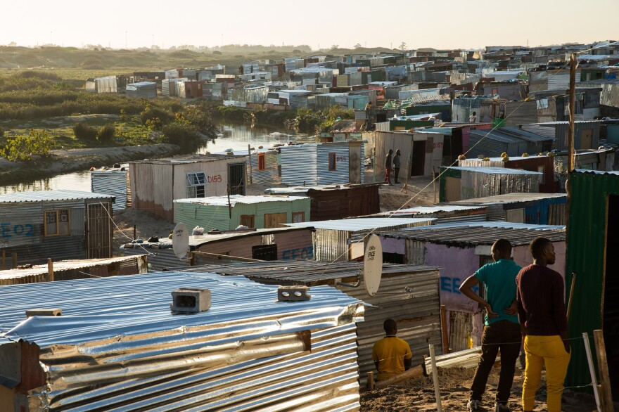 """Izwelethu, also known as """"Covid,"""" is an illegal settlement outside Cape Town comprising more than 800 tin shacks and 3,000-plus residents. It was started in March, when South Africa's national lockdown began. Some roofs are secured with bricks. With the winds of summer now blowing, more bricks will likely be needed."""