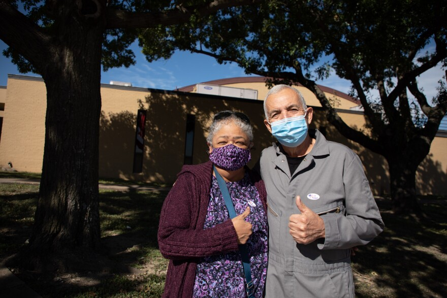 Joe and Arlene Ponce pose with masks on and thumbs up.