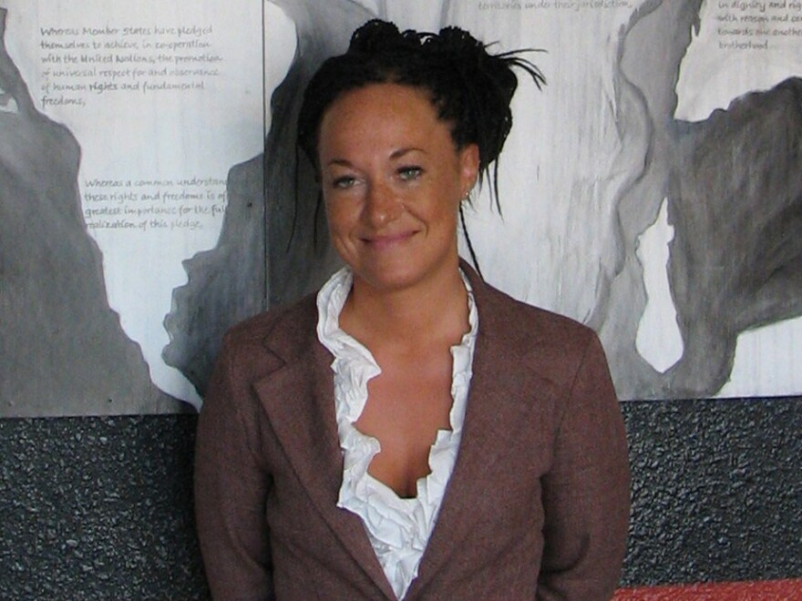 In this in July 2009 photo, Rachel Dolezal stands in front of a mural she painted at the Human Rights Education Institute's offices in Coeur d'Alene, Idaho.
