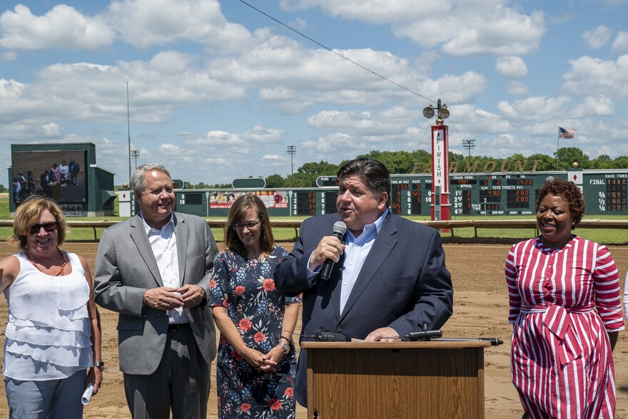 Illinois Gov. J.B. Pritzker addresses the crowd at Fairmount Park on July 30. He signed into law a gaming expansion that helps increase the tracks racing days to 100.