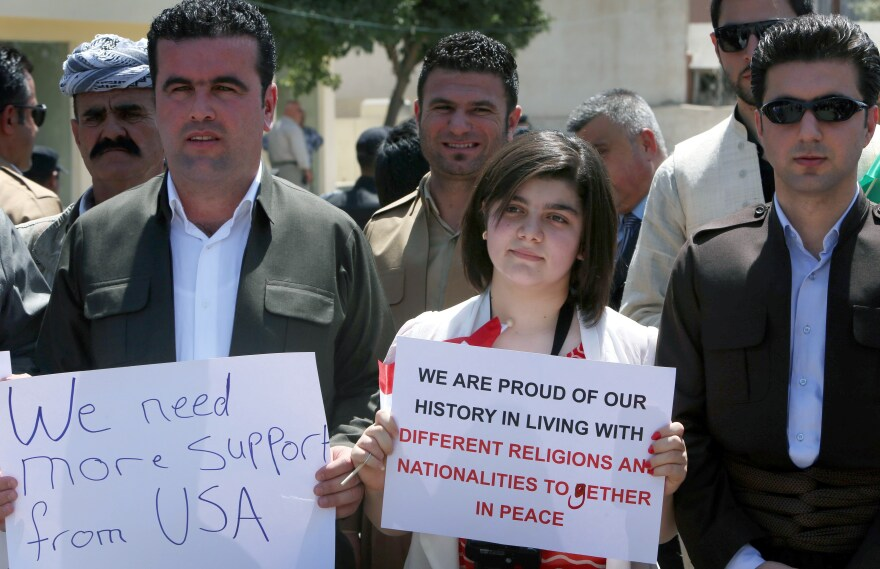 A group consisting mainly of Iraqi Christians hold signs during a rally in front of the U.S. consulate in Erbil, capital of the autonomous Kurdish region of northern Iraq, calling for more support and thanking the US. for air strikes aimed at halting the advance of Sunni Islamic State militants.