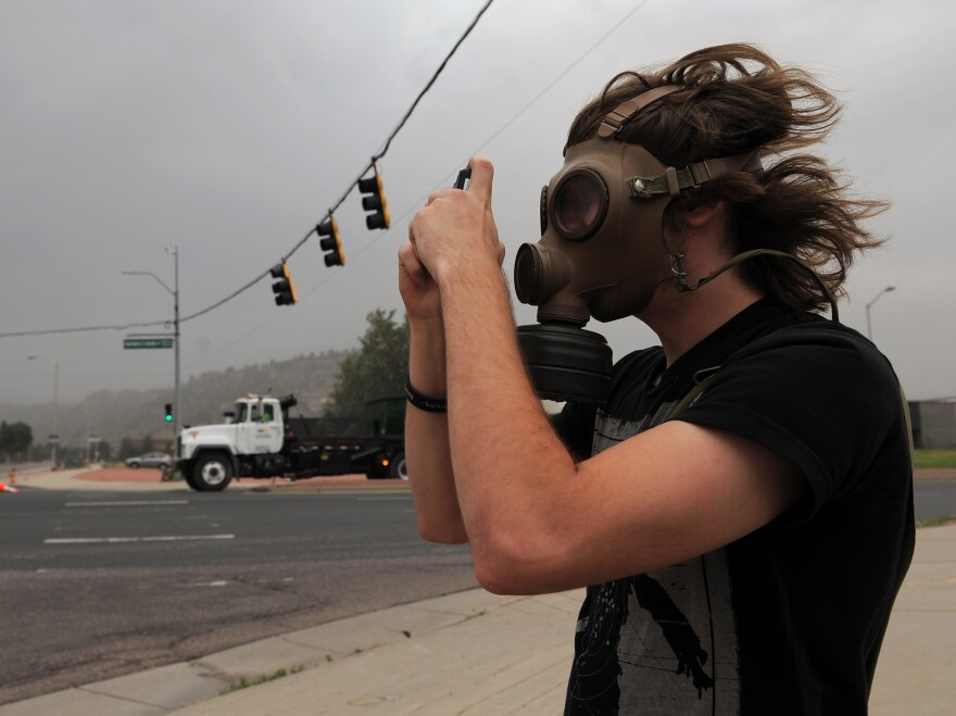 Mikke Carlson took photos of the smoke from the Waldo Canyon fire while wearing a gas mask on Wednesday in Colorado Springs, Colo.