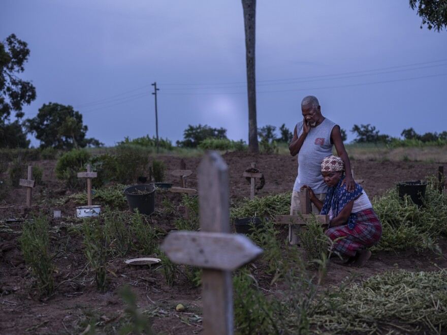 Siblings Luis Chopace and Mariamo Chopace at the grave of their sister Sumbo Chopace, who was killed when her home collapsed during Cyclone Idai. Mozambique's government is struggling to make the country more resilient in response to extreme weather.