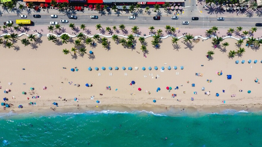 This is a stretch of Fort Lauderdale beach with water, sand, chairs with umbrellas, palm trees, and a road nearby with motorists. This beach may look very different in the coming year due to sea level rise.