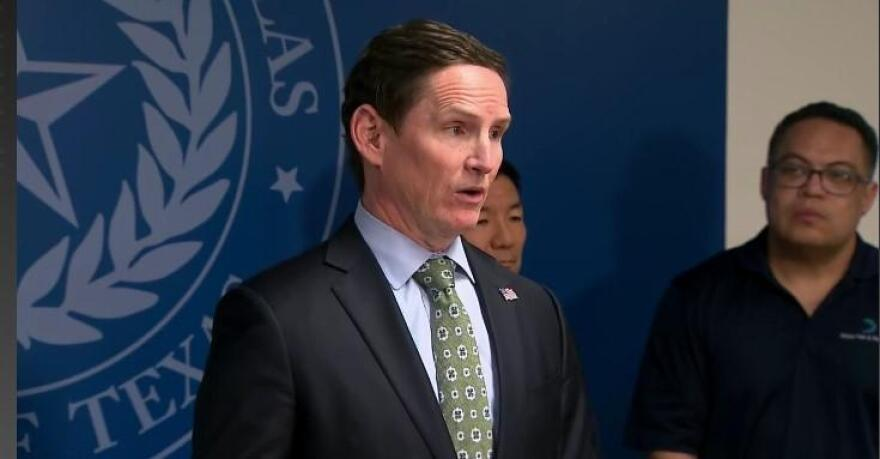 Dallas County Judge Clay Jenkins at a press conference in front of a seal for the state of Texas.