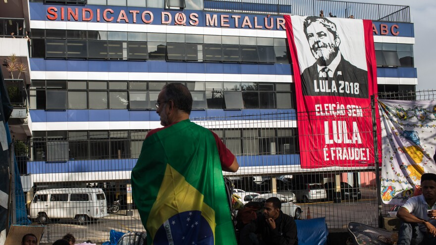 A supporter of former President Luiz Inacio Lula da Silva waits in front of the building where Lula holed up after defying a court order to turn himself in.