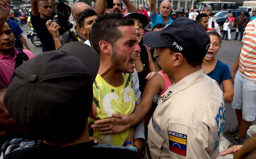 An angry man outside a grocery store argues with a policeman in Caracas, Venezuela, on June 8 amid the country's ongoing food shortages. After waiting for hours, customers began protesting, an increasingly common occurence in Venezuela, which is suffering a severe economic crisis.