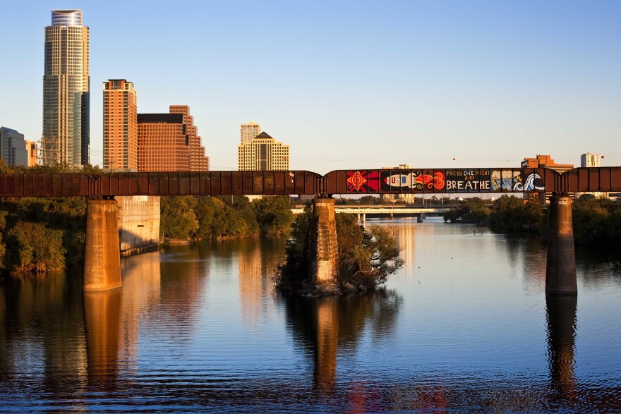 """The train bridge over Lady Bird Lake, as seen in 2010. A mural that says """"Focus One Point and Breathe"""" with a rocketship to the left and a stormcloud and a wave to the right."""