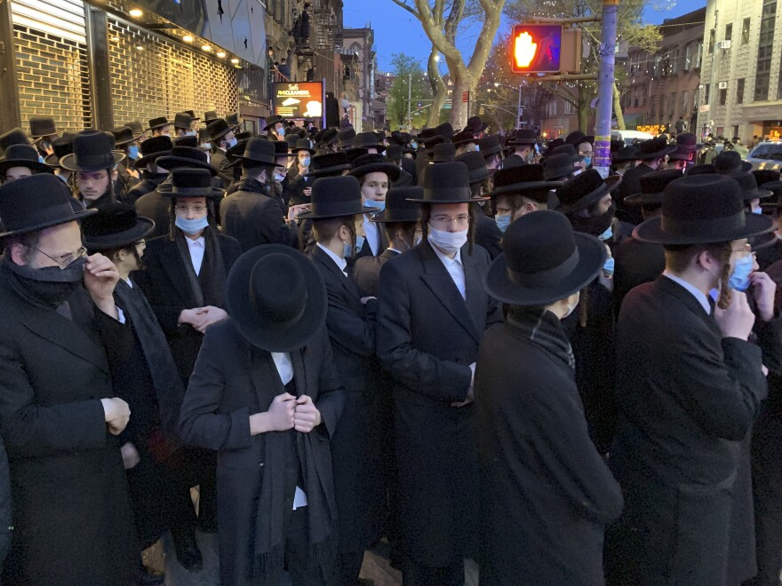 "Hundreds of mourners gather in Brooklyn on April 28, to observe a funeral for Rabbi Chaim Mertz, a Hasidic Orthodox leader whose death was reportedly tied to the coronavirus. Mayor Bill de Blasio chastised ""the Jewish community"" following the breakup of the large funeral that flouted public health orders."