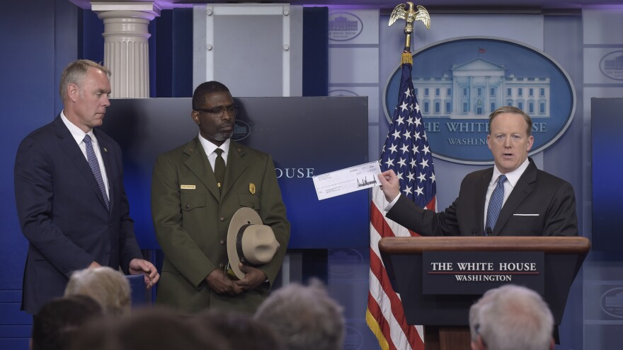 White House press secretary Sean Spicer holds up a check during the daily briefing at the White House on Monday with Interior Secretary Ryan Zinke, left, and Harpers Ferry park superintendent Tyrone Brandyburg.