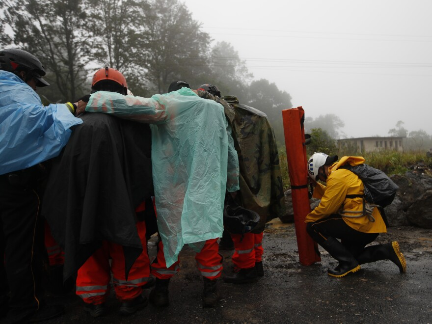 Volunteer firefighters huddle in prayer before beginning a search and rescue operation in San Cristobal Verapaz, Guatemala, Nov. 7, in the aftermath of Hurricane Eta.