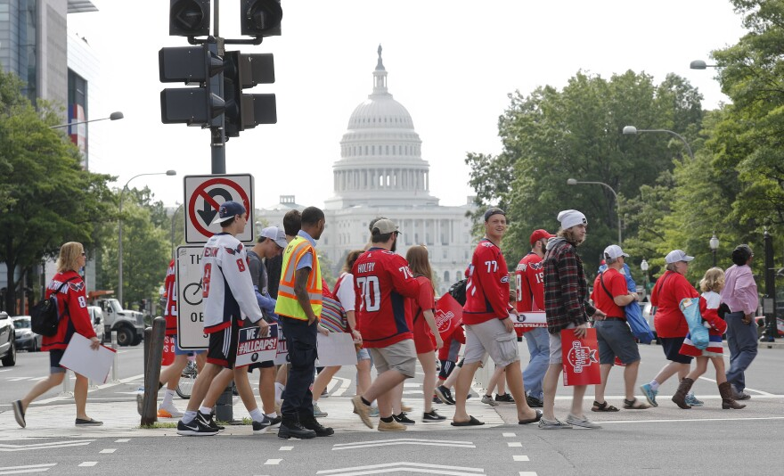 Washington Capitals fans cross Pennsylvania Avenue as they head toward the Stanley Cup victory parade route on the National Mall in Washington on Tuesday.