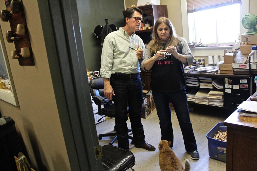 """General Manager Phil Morgan and Plant Manager Ardell Brown discuss materials for a style of corn cob pipes at the Missouri Meerschaum Company. The cat lives in the plant and is named """"Cob."""""""