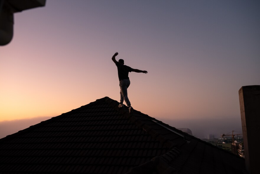 Zip Zap perfomer Jason Barnard climbs on a rooftop near his home in Green Point, Cape Town, South Africa. He's best known for his juggling skills and clown act and also works as an instructor.
