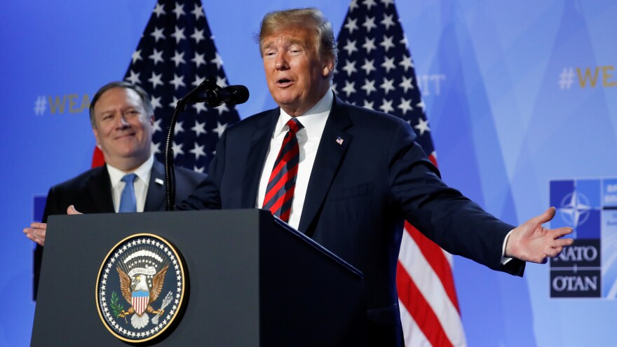 President Trump said Thursday that he has succeeded in getting U.S. allies to pledge more money for the alliance. Secretary of State Mike Pompeo looked on at a news conference after the NATO summit in Brussels.