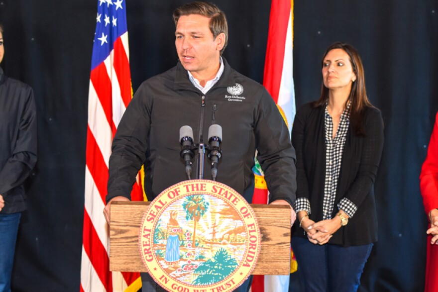 DeSantis standing at a podium in front of US Flag
