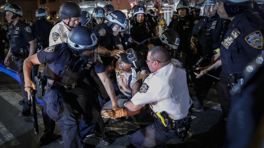 A protester is arrested on Fifth Avenue in Manhattan by New York City Police officers on Thursday.