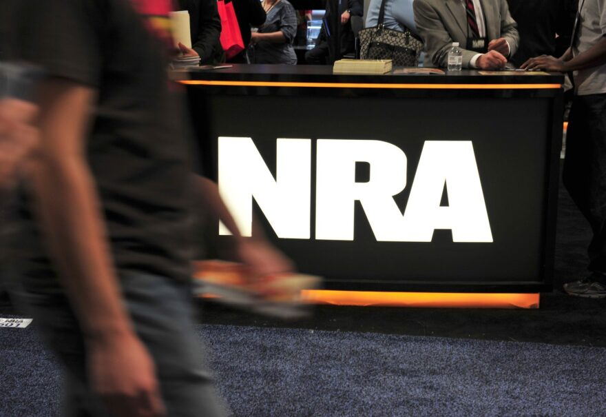 A convention goer passes the NRA desk at the 2015 NRA Annual Convention in Nashville, Tennessee.