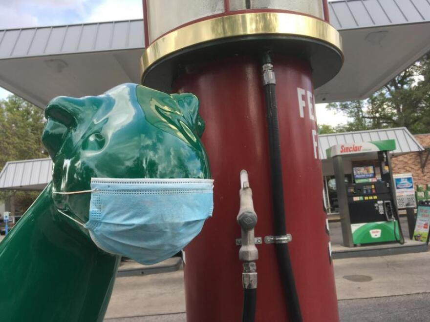 The dinosaur outisde a Sinclair gas station in Boise, Idaho wears a mask. The oil industry in the West relies on the whims of the global economy and the pandemic has ravaged it, forcing thousands of layoffs across the country.