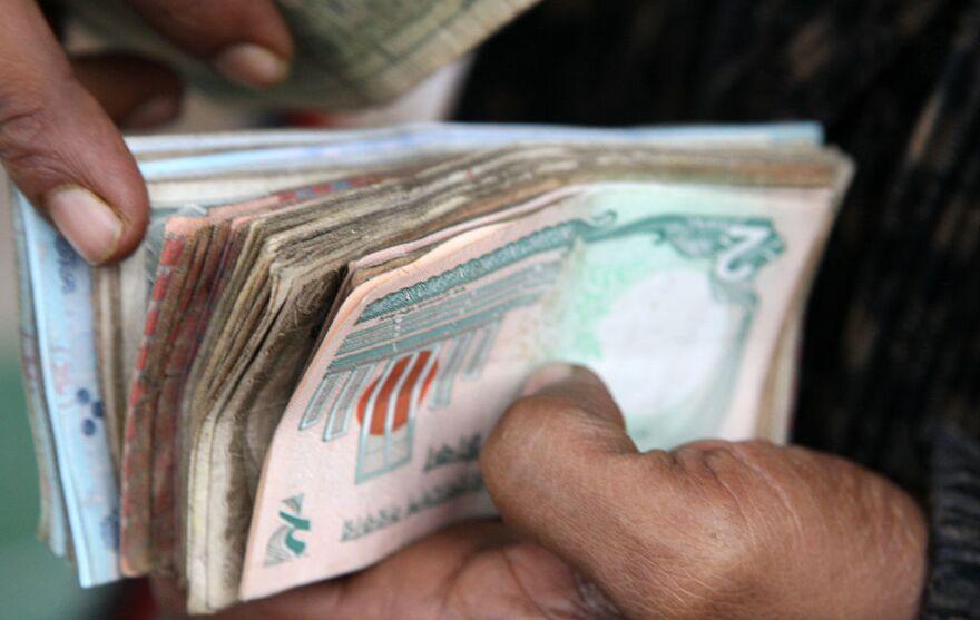 A vendor counts bank notes at a market in Dhaka, Bangladesh.